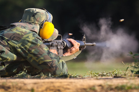 firing: Soldier shooting rifle gun to target with bullet cartridge in the air