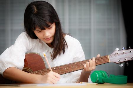 Jong Aziatisch meisje speelt gitaar en probeert muziek componist, lied schrijver te zijn Stockfoto