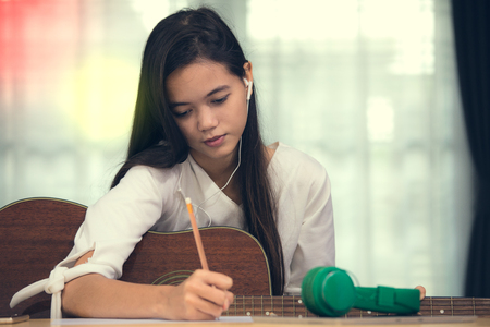 Young Asian girl playing guitar and try to be music composer, song writer Banco de Imagens - 80330526