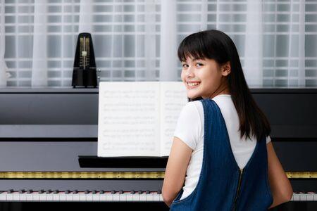 Jonge mooie Aziatische meisje, zittend aan een piano met vervaging muziek blad en metronoom, het ritme-apparatuur