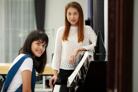 metronome: Two Asian family, mother and daughter learn to play piano together in home, mom in blur background
