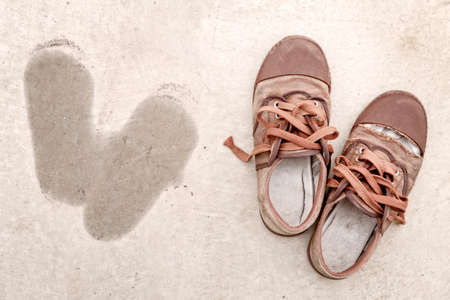 Old shoes on dirty ground with footprint beside Foto de archivo