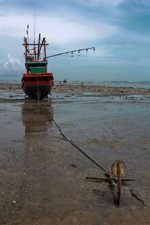 Fishing boat stuck on shore with an anchor photo