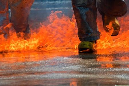 Two men in firefighting suit walking on fire