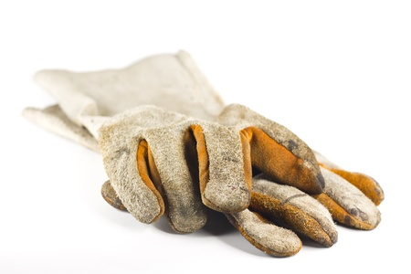Dirty old leather gloves  shallow focus isolated on white background photo