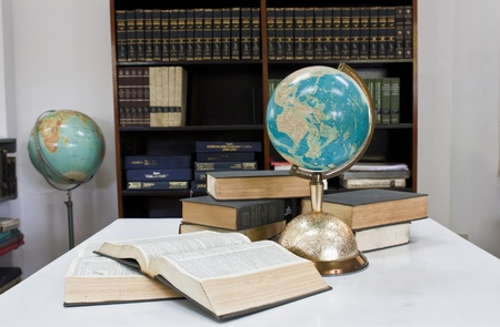 Pile of books and globe balls in library