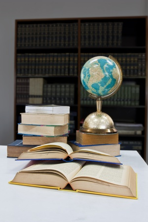 Pile of books and globe balls in library photo