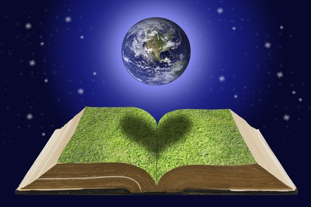 Earth over open book that has grass on it page on space background photo