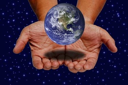 Earth on hands on space and stars background photo