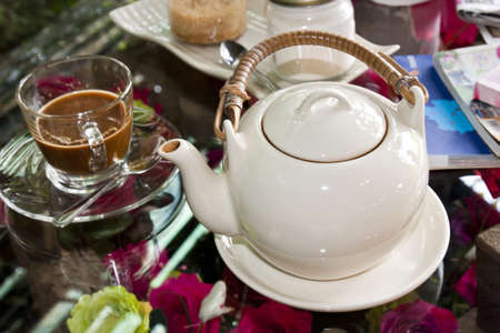White tea pot pottery and a cup of coffee on glass table photo