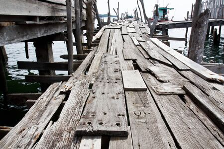 old pier: Old wooden fishing bridge to the sea Stock Photo