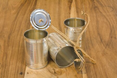 Three open cans on wooden table photo