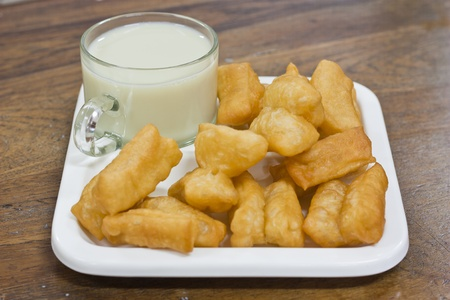 Deep fried dough sticks and a cup of soybean milk on tray photo