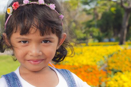 Little asian girl smile with shallow focus on flowers background photo