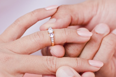 Male hand wear diamond ring in to female finger Stock Photo - 11698021