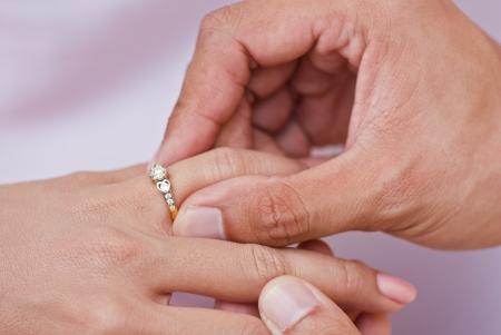 약혼: 여성의 손가락에있는 남성의 손에 착용 다이아몬드 반지 스톡 사진