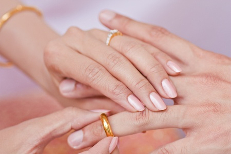 Female hand wear golden ring in to male finger photo