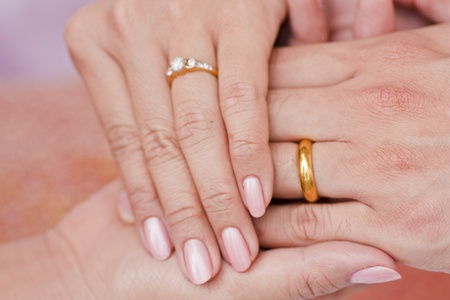 girl with rings: Female and male hand wearing engagement ring hold hand in hand Stock Photo