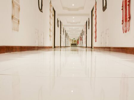 Corridor with white ceiling and reflect white floor in low angle photo