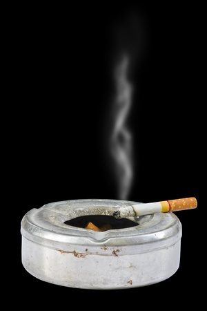 Cigarette on ash tray on black background