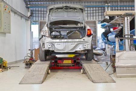 car repair shop: Repairing car lifted in garage
