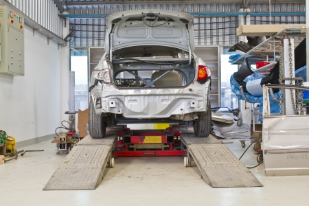 Repairing car lifted in garage
