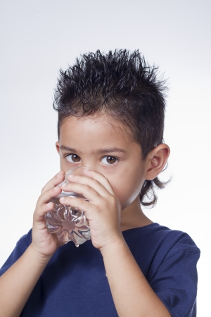 caucasian water drops: Little boy drinking water on white background Stock Photo