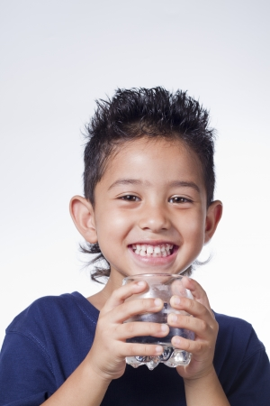 Little boy hold glass of water on white background Standard-Bild