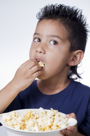 eating popcorn: Little boy and pop corn on white background Stock Photo