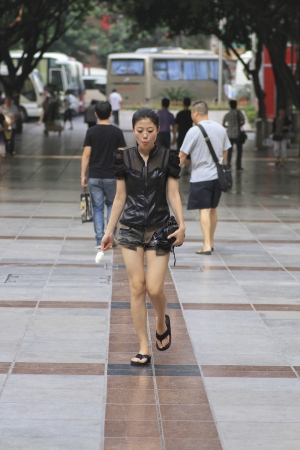 eats: CHONGQING,CHINA- AUGUST 2012:Unknow girl walks while eats ice cream to reduce heat of heat wave insummer of China