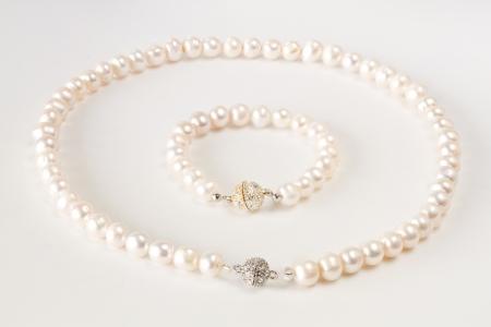 Pearls necklace bracelet on white background photo