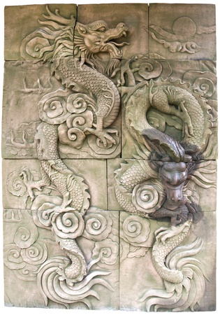 stone carving: Ancient sculpture dragon stone wall isolated on white background Stock Photo