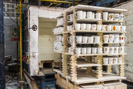Ceramic mugs on racks in front of kiln in ceramic factory.
