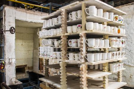 Tazas de cerámica en los estantes delante del horno en la fábrica de cerámica.