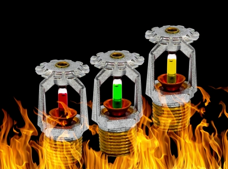 Close up image of fire sprinkler with fire in background. Fire sprinklers are part of an integrated water piping system designed for life and fire safety. photo