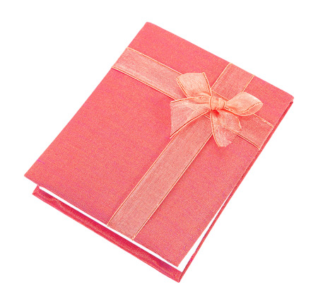 Notebook cover made of red Linen fabric with bow for souvenir isolated on white background photo