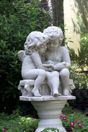 Little cupid statue isolated in the garden background.
