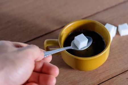 The hand is filling the sugar into the coffee.
