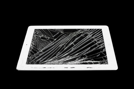 tablet computer with broken glass screen isolated on black background