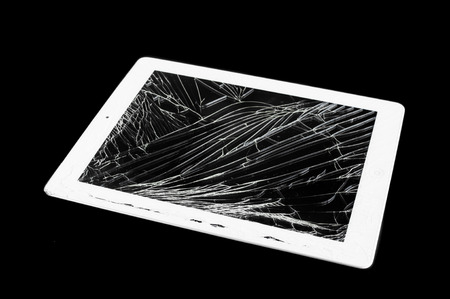 tablet computer with broken glass screen isolated on black background photo