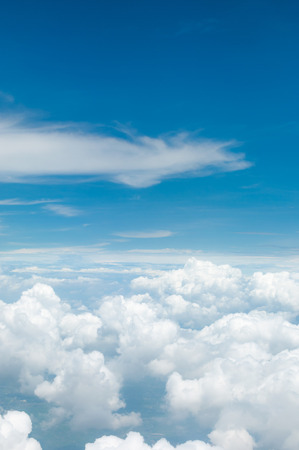cloud drift: fluffy white clouds and blue sky background seen from airplane Stock Photo