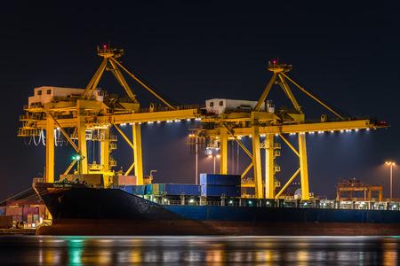 camion grua: Buque de carga de carga de trabajo con puente grúa en astillero en la noche para la exportación de importación logística