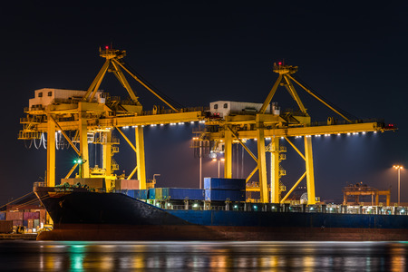 container cargo freight ship with working crane bridge in shipyard at night for logistic import export