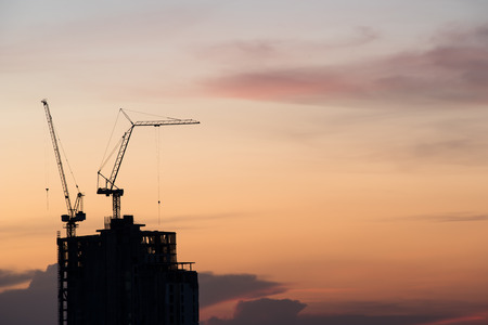 site construction: silhouette of crane and building construction at sunset