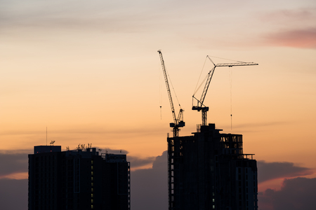 site construction: silhouette of crane and building at sunset Stock Photo
