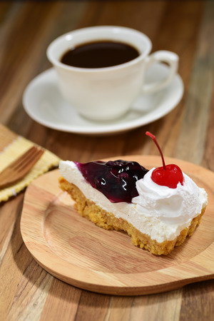 slice of blueberry cheese cake on wooden table with a coffee cup