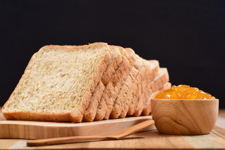 slices of bread: slices bread with orange jam on wooden table