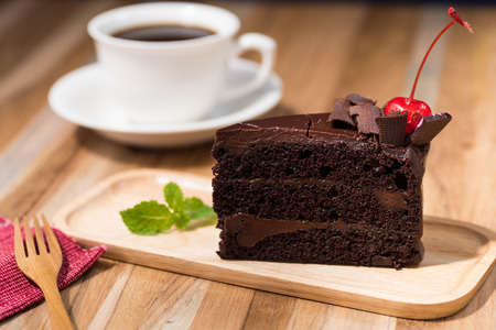 pieces: chocolate cake on wooden table with a coffee cup