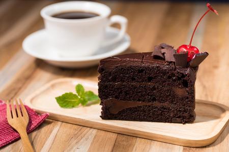 rebanada de pastel: pastel de chocolate en la mesa de madera con una taza de café Foto de archivo