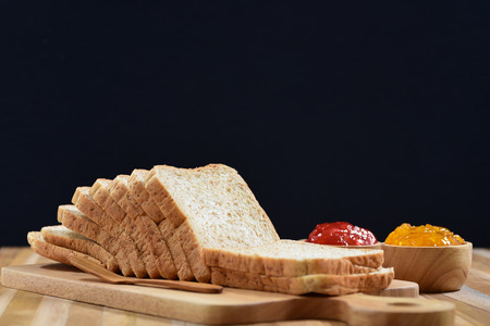 slices of bread: slices bread with fruit jam on wooden table Foto de archivo
